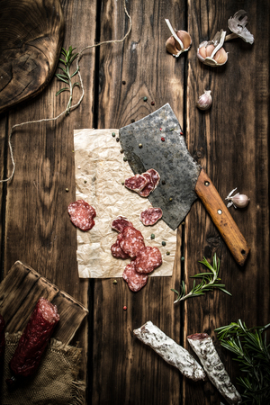 hatchet: Salami with an old hatchet, and different spices. On wooden background.