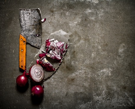 hatchet: Sliced red onion and an old hatchet on a stone stand. On a stone background.