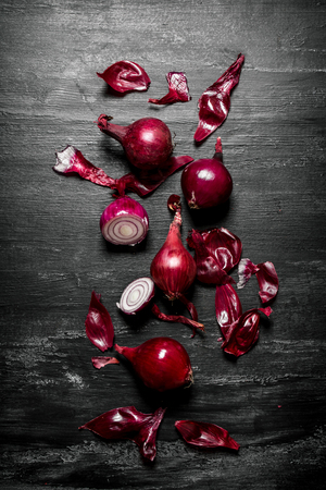 poignant: Red onion . On the black rustic background.