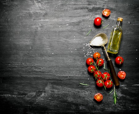 black olives: Fresh tomatoes with olive oil and a spoon of salt. On black rustic background. Stock Photo