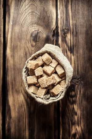 refined: Cane sugar refined in the bag. On the wooden background.