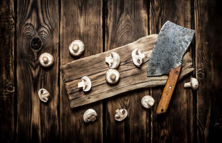 hatchet: Sliced fresh mushrooms old hatchet. On wooden background.