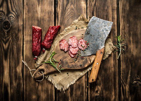 hatchet: Sliced salami with a hatchet and rosemary. On wooden background. Stock Photo