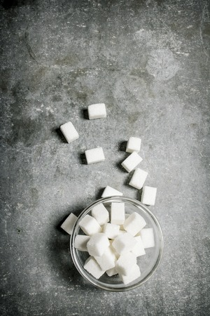 refined: Refined sugar in a glass saucer. On a stone background.