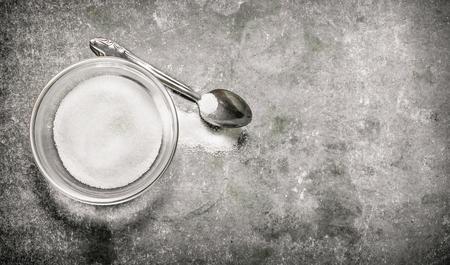 cuchara: Copa de azúcar y una cuchara. Sobre un fondo de piedra. Foto de archivo