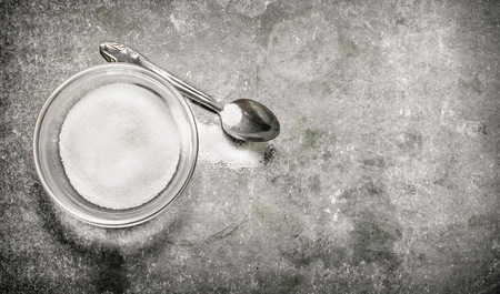 sugar spoon: Sugar Cup and spoon. On a stone background. Stock Photo