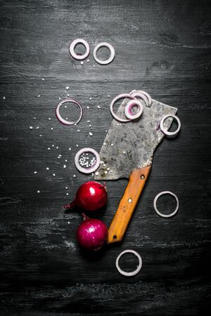 hatchet: Onion rings with a hatchet. On the black rustic background.