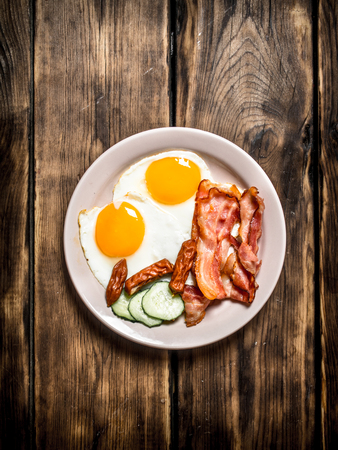 english cucumber: plate of fried eggs, bacon , cucumber and smoked sausages. On a wooden table. Stock Photo