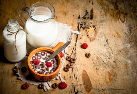 chocolate cereal: Chocolate cereal with raspberries and milk. On wooden background. Stock Photo