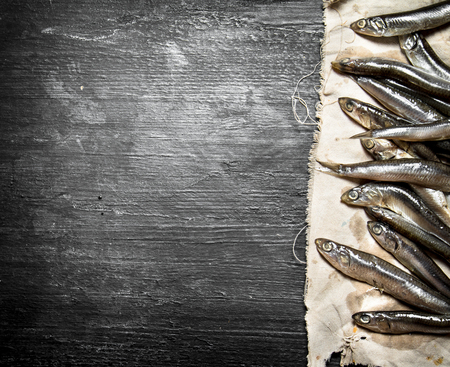 sprat: Sprat on the old fabric. On a black wooden background. Stock Photo