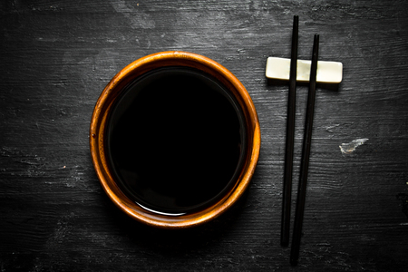 chop stick: Soy sauce in a bowl and chopsticks. On a black wooden background.