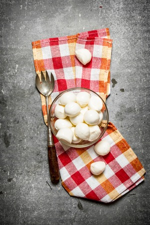 marble stone: Mozzarella in a bowl and old fork . On the stone table.