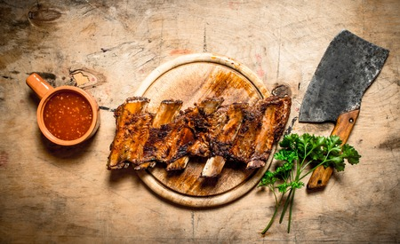hatchet: Barbecued ribs with tomato sauce and a carving hatchet. On wooden background.