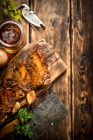 hatchet: Pork ribs grilled with a meat hatchet and beer. On a wooden table.