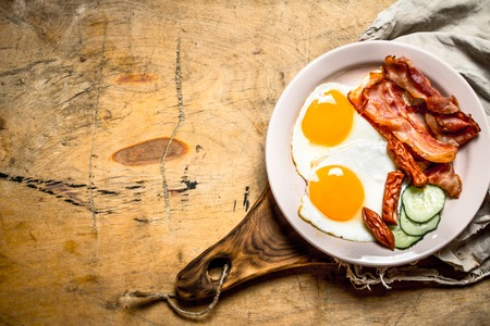 english cucumber: fresh Breakfast plate. Fried eggs with bacon and tomatoes. On a wooden table. Stock Photo