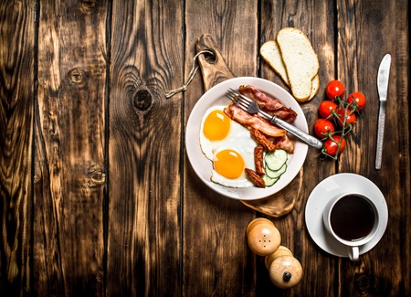 beck: Fresh Breakfast with Cup of coffee, fried Beck with eggs and tomatoes. On a wooden table. Stock Photo