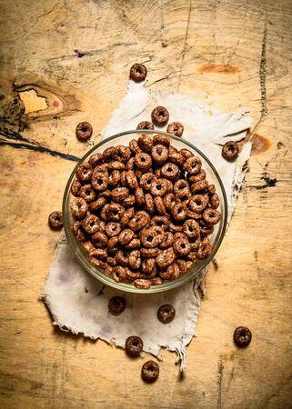 chocolate cereal: Chocolate cereal in a Cup. On a wooden background.