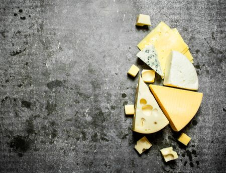Pieces of flavored cheese . On the stone table.