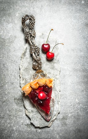 golden shovel: piece of cherry pie. On the stone table. Stock Photo