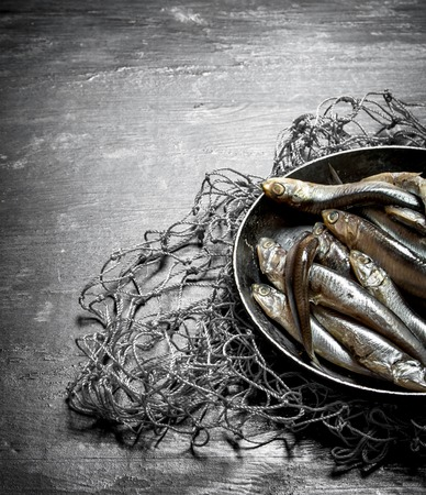 Sprats in a bowl on the fishing net. On a black wooden background.