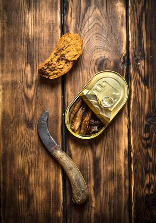 sardine can: Smoked sprats with rye bread. On wooden background.