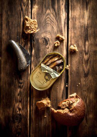 sprat: Smoked sprats with rye bread. On wooden background.
