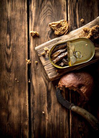 sardine: Smoked sprats with rye bread. On wooden background.