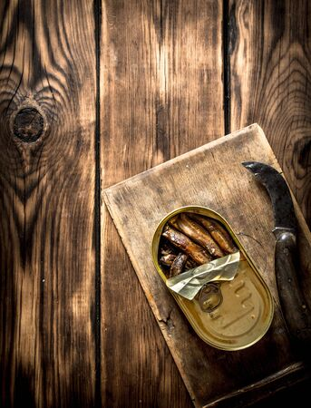 sardine can: Smoked sprats in oil with an old tin with a knife. On wooden background.