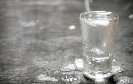 stone cold: The glass of cold vodka. On the stone table.