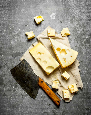 hatchet: Hatchet and pieces of fresh cheese. On the stone table.