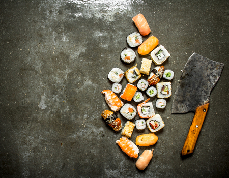 free backgrounds: Various Japanese sushi rolls with an axe for cutting. On the stone table.