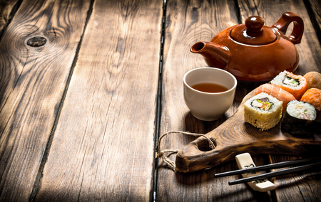 free backgrounds: Sushi and rolls with herbal tea. On a wooden table.