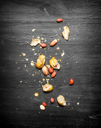 shelled: Shelled peanuts with the shell. On the black wooden table. Stock Photo