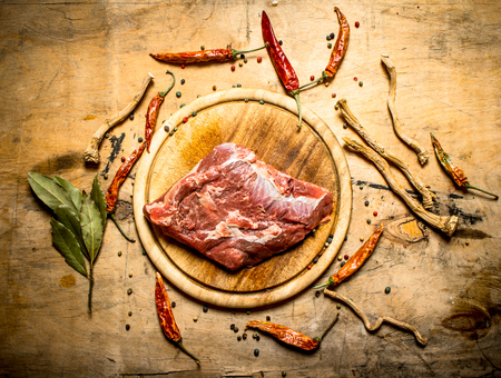 Raw pork with spices and bay leaves. On wooden background.