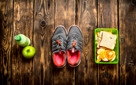 Breakfast in the morning. Sandwiches , fruit ,milkshake and sports sneakers Stock Photo - 62760430