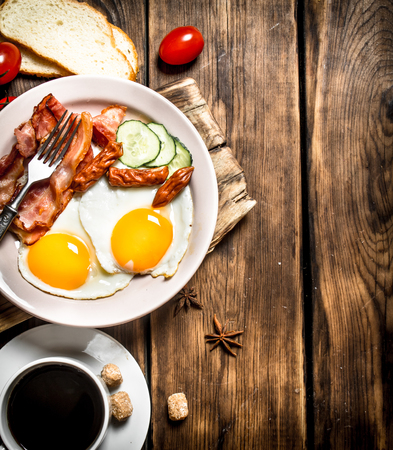 Fresh Breakfast with Cup of coffee, fried bacon with eggs and tomatoes. On a wooden table.