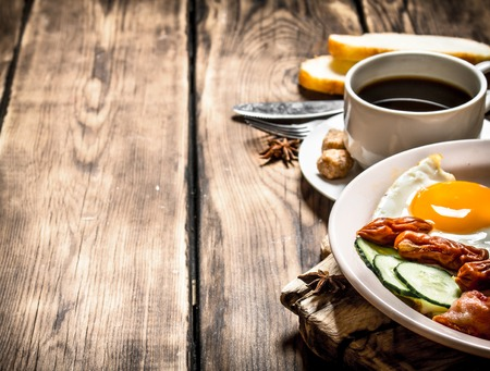 fresh Breakfast. Cup of coffee , fried bacon with eggs and smoked sausage. On wooden background. Stock Photo