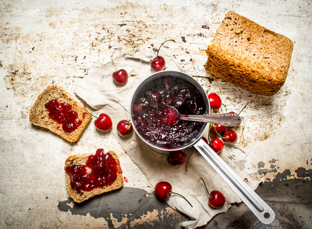 sour cherry: The sandwich with sour cherry jam. On rustic background.