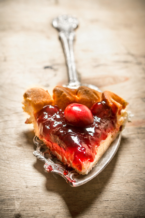 golden shovel: piece of fresh cherry pie. On a wooden table Stock Photo
