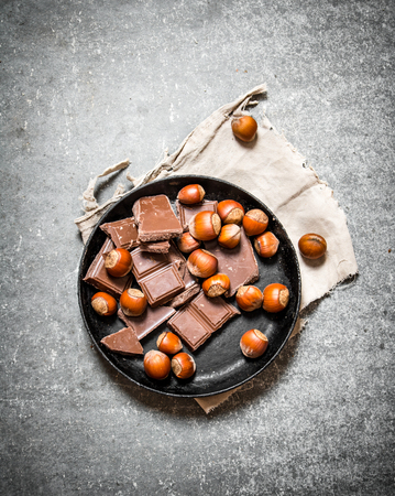 Pieces of chocolate with nuts on the old plate. On the black wooden table.