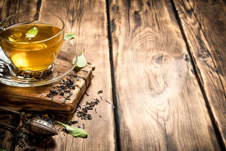 fragrant tea with infuser spoon. On wooden background.
