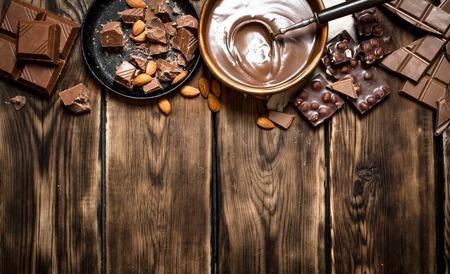 チョコレートとナッツのスライスとチョコレート クリーム。木製のテーブル。
