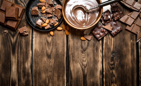Chocolate cream with slices of chocolate and nuts. On a wooden table. Stock Photo