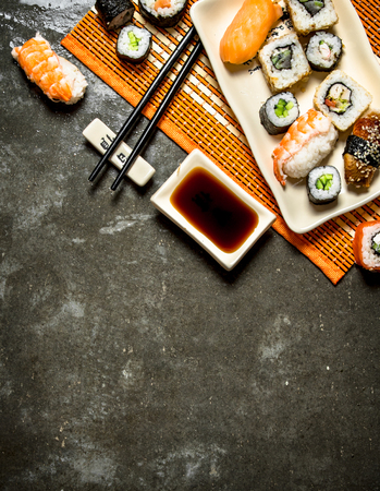 free background: Japanese food . The rolls and sushi with soy sauce on bamboo stand.