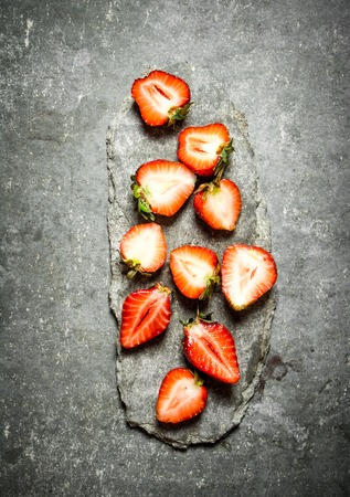halved: Ripe halved strawberries. On the stone table.