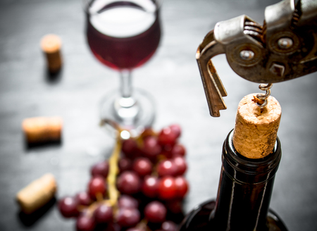 Bottle of red wine with a corkscrew. On a black wooden background. Stock Photo