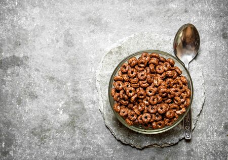 chocolate cereal: Chocolate cereal in a Cup. On the stone table.