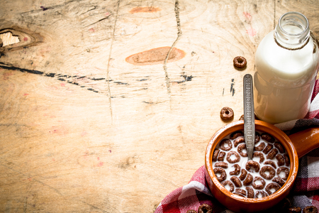 chocolate cereal: Healthy food. Chocolate cereal with milk. On wooden background.
