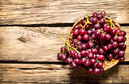 Red grapes in a basket. On a wooden table.