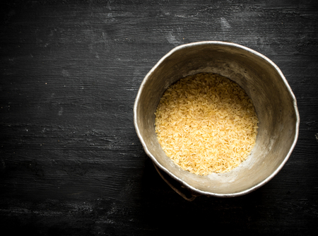 unboiled: Rice in an old pot. On a black wooden background.
